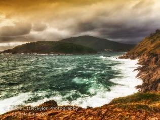 warm sunset coastline dark clouds