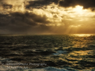 warm soft sunset sunrays on the ocean dark clouds Promthep